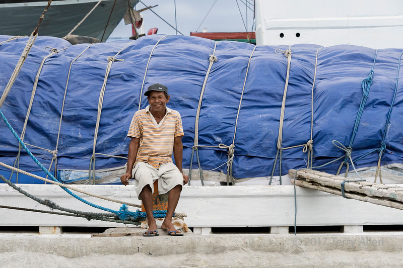Smiling seaman sitting on a bollard with his sleeping cat at his feet, next to a pinisi, Sunda Kelapa Harbour, Jakarta, Indonesia