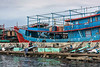 Harbour scene with fish carts, fish boxes and fishing boats, Pasar Akan Harbour, Jakarta, Indonesia