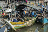 Fisherman sitting in his traditional fishing boat, Sunda Kelapa Harbour, Jakarta, Indonesia