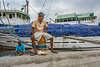 Portrait of a seaman and his sea-cat next to pinisis, Sunda Kelapa Harbour, Jakarta, Indonesia