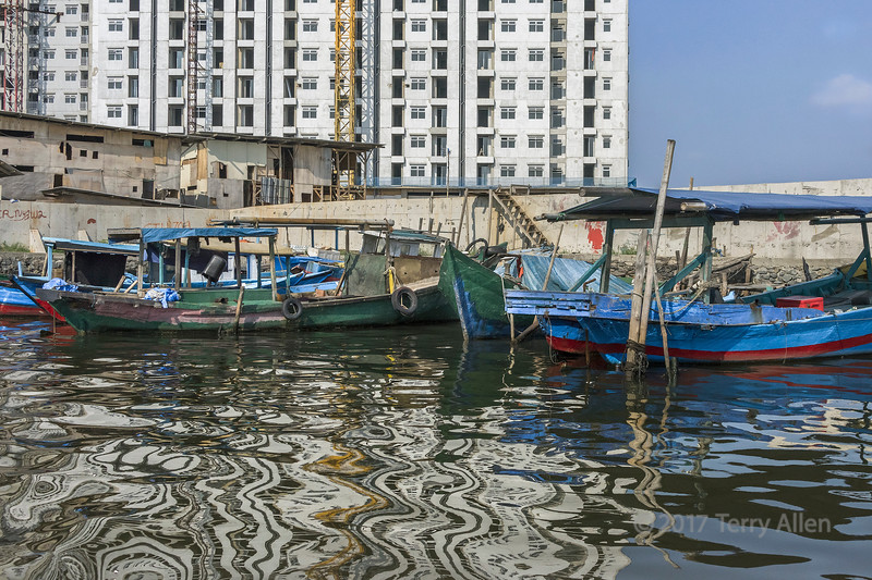 New highrise and old wooden runabouts with reflections, Sunda Kelapa Harbour, Jakarta, Indonesia