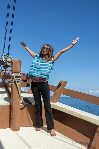 Joy of sailing, woman on old pinisi-style wooden boat, off Labuan Bajo, West Flores Island, Indonesia