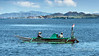 Couple fishing in a wooden outrigger fishing boats with long tail engine under deck cowling, off Labuanbajo, West Flores, Indonesia