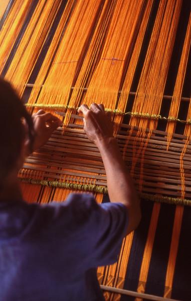 Woman weaves using loom, Waikabubak, Sumba, Indonesia.