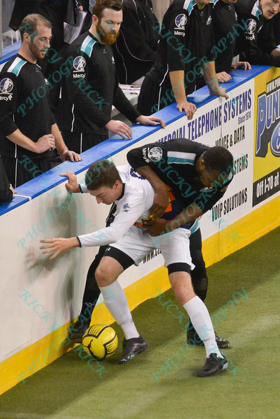 St. Louis Ambush forward ODAINE SINCLAIR (12) and Tacoma Stars defender TREVOR MCDONALD (8) battle along the boards for the ball during a regular season Major Arena Soccer League (MASL) game between the St, Louis Ambush and the Tacoma Stars played at the Family Arena in St. Charles, MO., where St. Louis defeats Tacoma by the score of 13-3