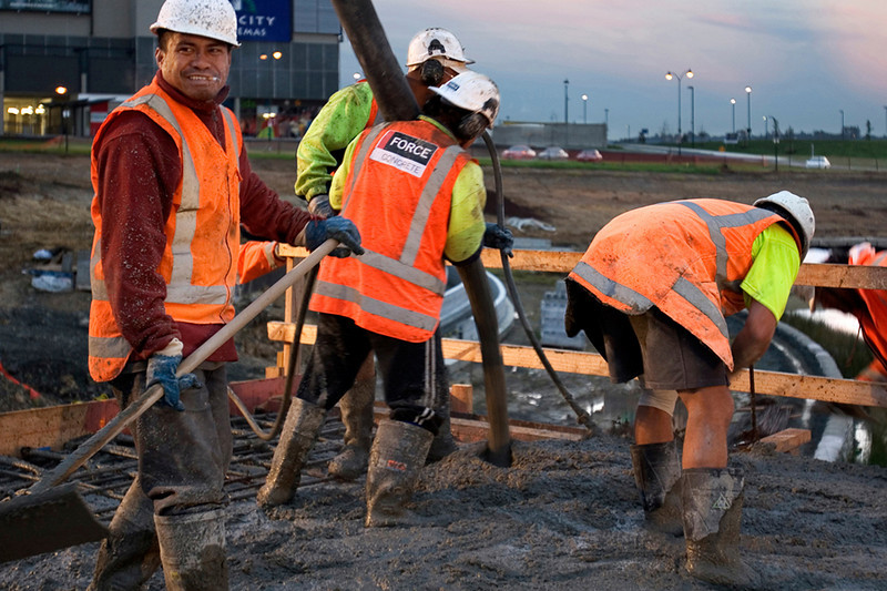 Working the concrete as it is poured onto bridge.