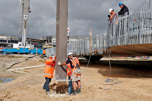 Guiding the post onto the foundation plate - the crane behind.