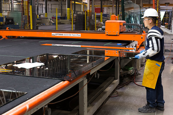 Engineer cutting large glass sheet at Hartung Glass.