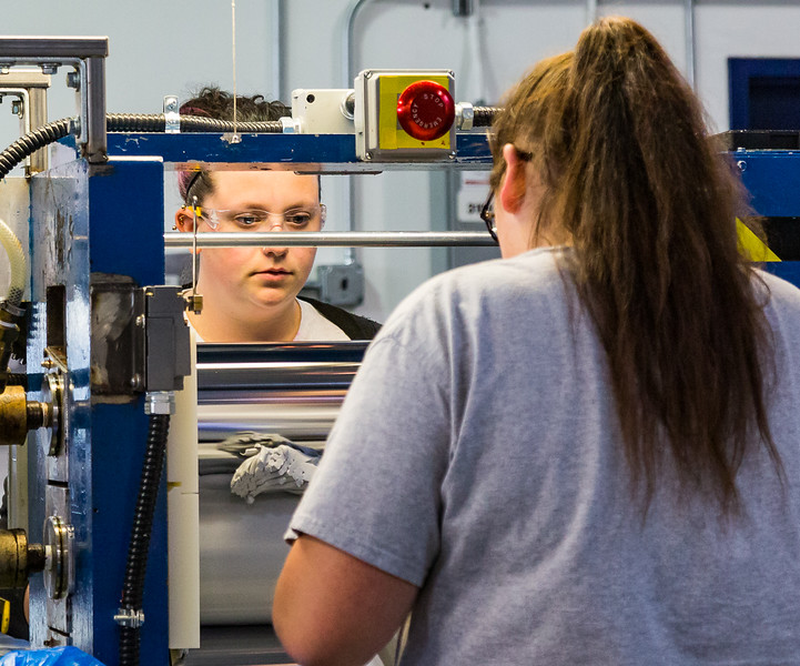 Women manufacturing gaskets on factory equipment.