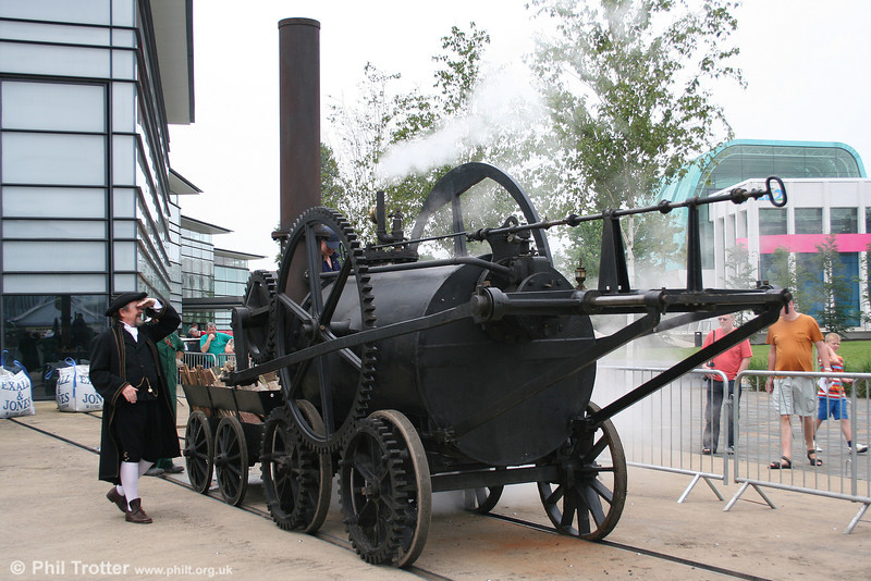 """On 31st May & 1st June 2008, the National Waterfront Museum of Wales in Swansea held a rare steaming of its 1981-built 4' 4"""" gauge replica of Trevithick's 4wG Penydarren locomotive. The original Penydarren locomotive made its first journey on 21 February 1804, hauling ten tons of iron, 70 passengers and five wagons on the nine-mile journey from Penydarren to the Merthyr to Cardiff Canal. Mr. Trevithick keeps an eye on the locomotive's boiler pressure on 1st June 2008."""
