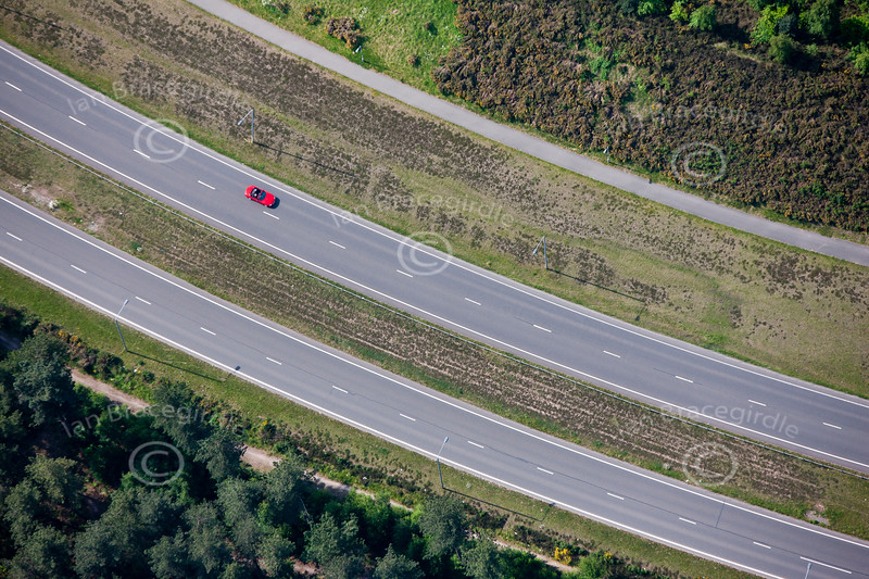 A stock aerial photo of road patterns with a single red sportscar.
