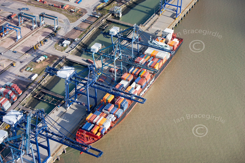 Aerial photo of colourful shipping containers being loaded onto a container ship at Tilbury Docks.