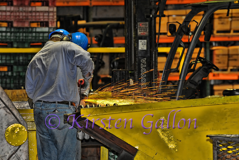 Sparks fly off of a part as these workers are in the finishing section of the plant.  They make everything look nice and shiny.