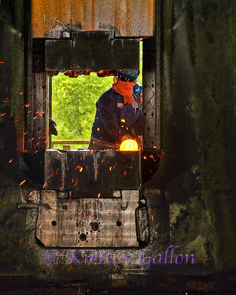 One of the workers handling a steel cylinder that is being forged into a part of some sort.