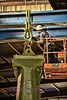One of the workmen putting together a large link that attaches the hammer frame to the hydraulic system for moving it into place in the pit.