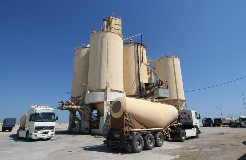 Cement factory with silos and trucks