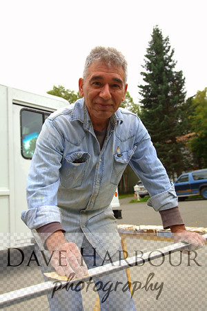 Happy Alaska carpenter, Tony Tanzi, smiling, sanding, Anchorage, Alaska.  A carpenter's hands.  Normal light cast....