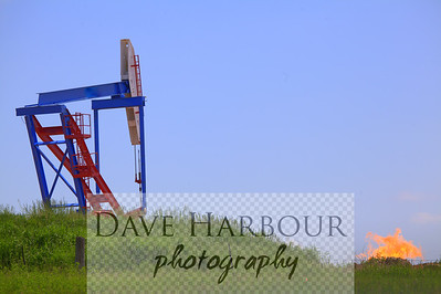 North Dakota oil pump with natural gas safety flare pit in background, Color.