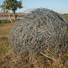 large ball of barbed wire rolled up and left in the field