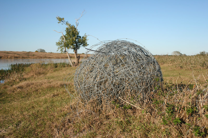 wide view of ball of barbed wire rolled up and left in a field