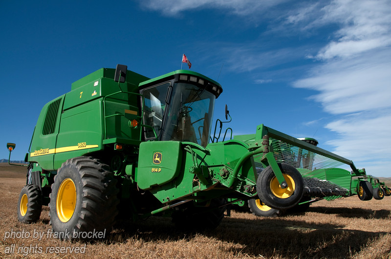 A couple of John Deere 9650 combines in a field in the foothills of Southern Alberta