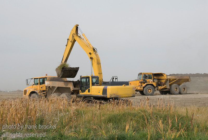 A shovel loading trucks at a new development in Calgary