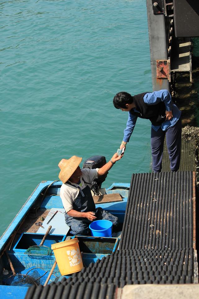 Local restaurant owner purchasing fish from fisherman, Sok Kwu Wan, Lamma Island, Hong Kong