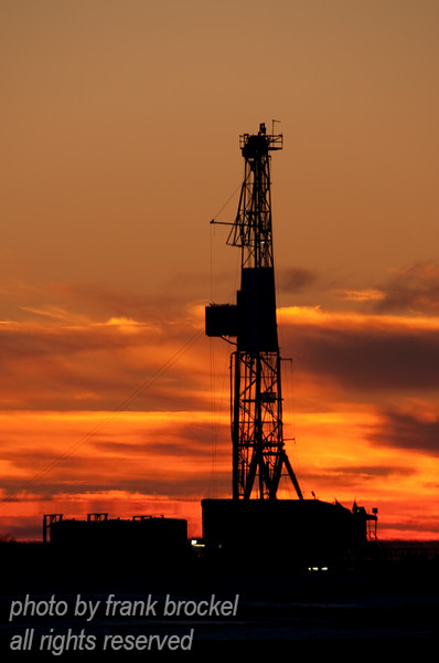 A drill rig owned by AKITA Drilling Ltd. is going full bore at -26Cwith a spectacular sunset as a backdrop.