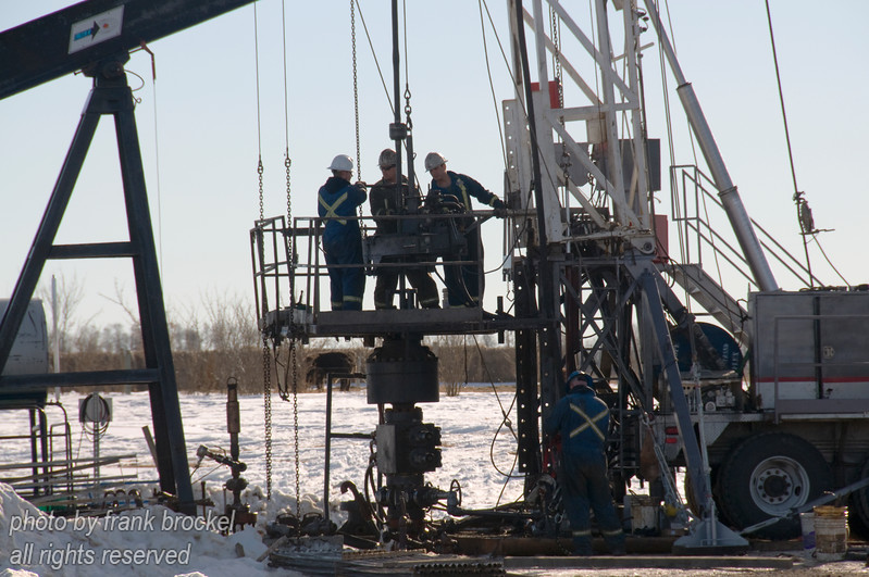Workers repairing a pumjack with service rig near Water Valley, Alberta