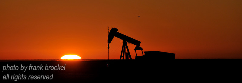 A pumpjack framed against a sun rise