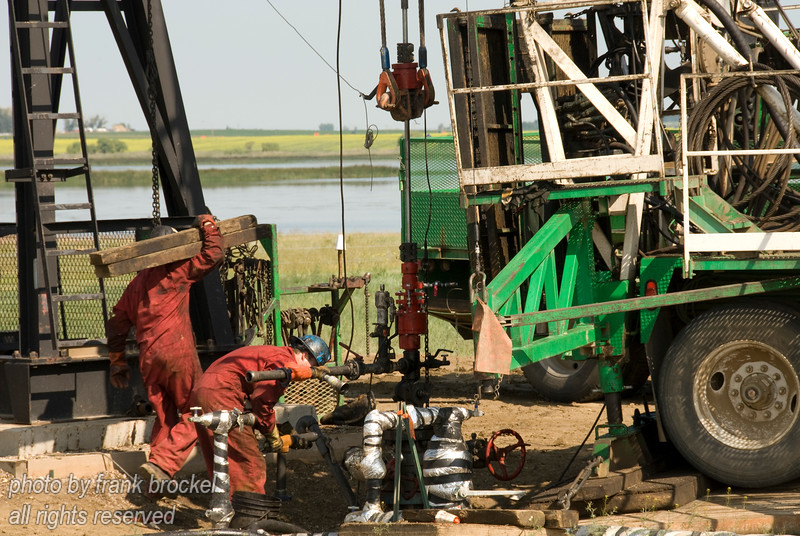 Workers fixing a pumjack with service rig near Brooks, Alberta
