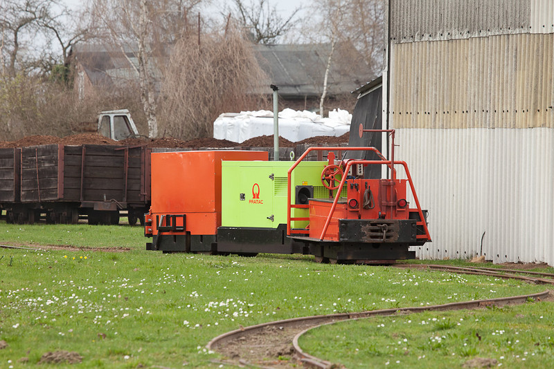 Detail view of the locomotive with a string of racks waiting to be unloaded. A number of white industrial-size peat bales stand ready to be shipped in the background.