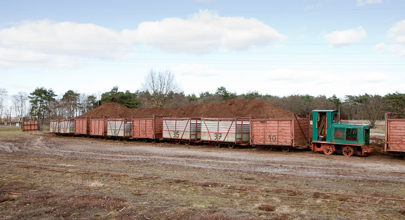 Loaded train parked in front of the peat pile waiting to be dumped.