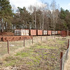 Stored empty racks and an allotment patch where employees grow their own veggies on the side. This is rabbit country - note fence posts made of rail sections.