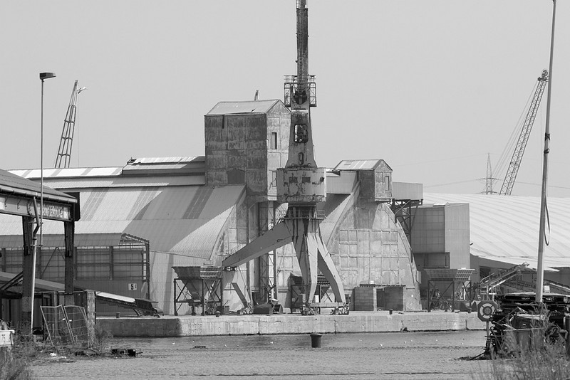 Timeless scene showing warehouses and a crane, covered in aggregate dust.