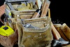 Closeup of rugged worn leather carpenters work bags with construction tools of the trade