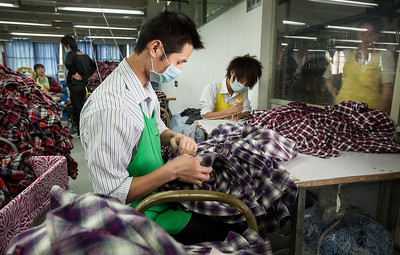 Workers process shirts at the Lever Style Inc. Guan Lan Town production facility for Shirts and Blouses in Shenzhen, Guangdong Province, China on Wednesday, Dec. 8, 2010. Photographer: Forbes Conrad/Bloomberg News
