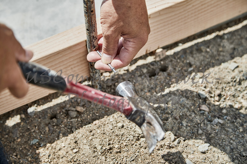 Man using a sledge hammer to fasten down a form stake