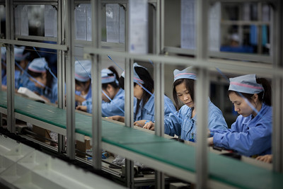 Workers labor in a PCB board assembly line at the ICCNexergy factory campus in QingXi, Dongguan, Guangdong Province, China.