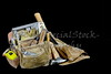 Rugged well used carpenters work bags with tools isolated on black