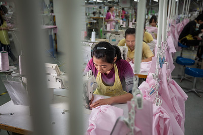 A worker assembles shirts at the Lever Style Inc. Guan Lan Town production facility for Shirts and Blouses in Shenzhen, Guangdong Province, China on Wednesday, Dec. 8, 2010. Photographer: Forbes Conrad/Bloomberg News
