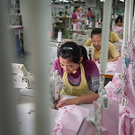 A worker assembles shirts at the Lever Style Inc. Guan Lan Town production facility for Shirts and Blouses in Shenzhen, Guangdong Province, China on Wednesday, Dec. 8, 2010. Photographer: Fo ...