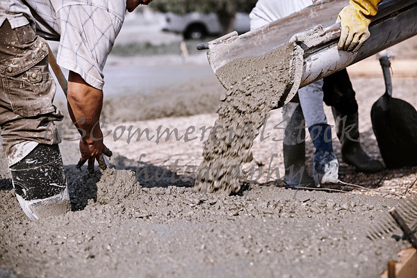 Closeup of construction workers pouring concrete