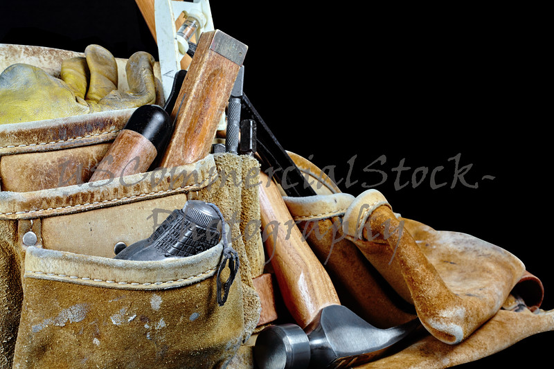 Closeup of Worn carpenters leather work belt with used construction tools isolated on black background with selective focus and copy space