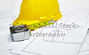 Blueprints with hardhat and tape measure
