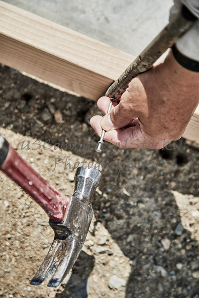 Man using a  hammer to fasten down a form stake