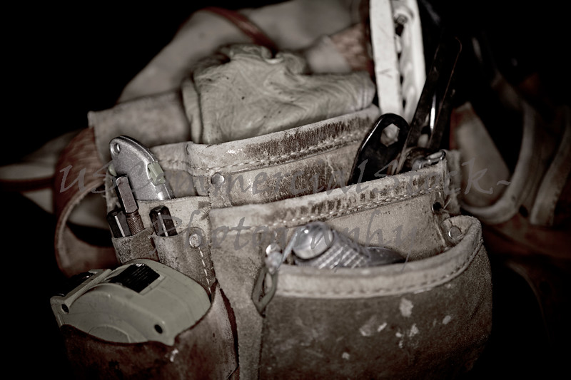Rugged worn leather carpenters work bags with construction tools in monotone isolated on black background
