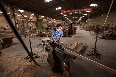 A worker operates a planer at the Hongyuan Furniture Company factory in Panyu, Guangzhou, Guangdong Province, China, on Wednesday, June 6, 2012. Photographer: Forbes Conrad