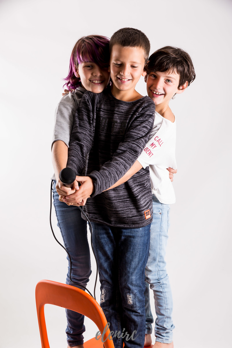 Nuria Rebull Logopeda Mollet del Valles reportaje corporativo de Elena Rubio fotógrafa infantil en elenircfotografia Tres niños juegan en una silla naranja con un micrófono