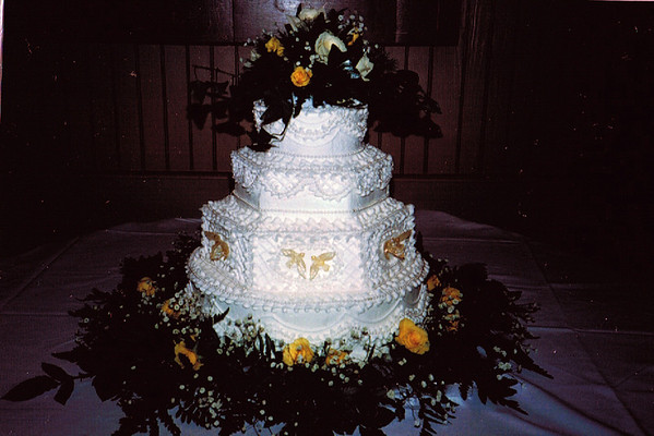 07 This hexagon and round cake has ruffles and beads with doves and fresh flowers to complete.